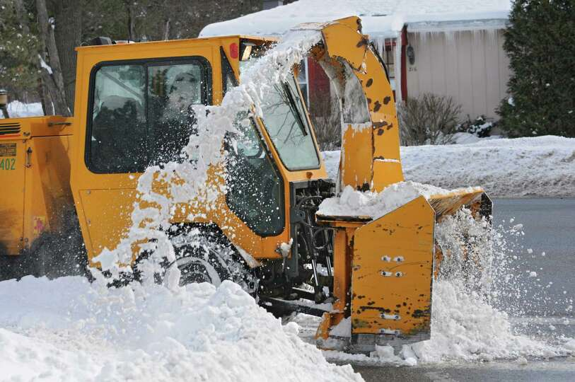 Industrial Snow Thrower : An industrial sized snow blower clears the sidewalk along
