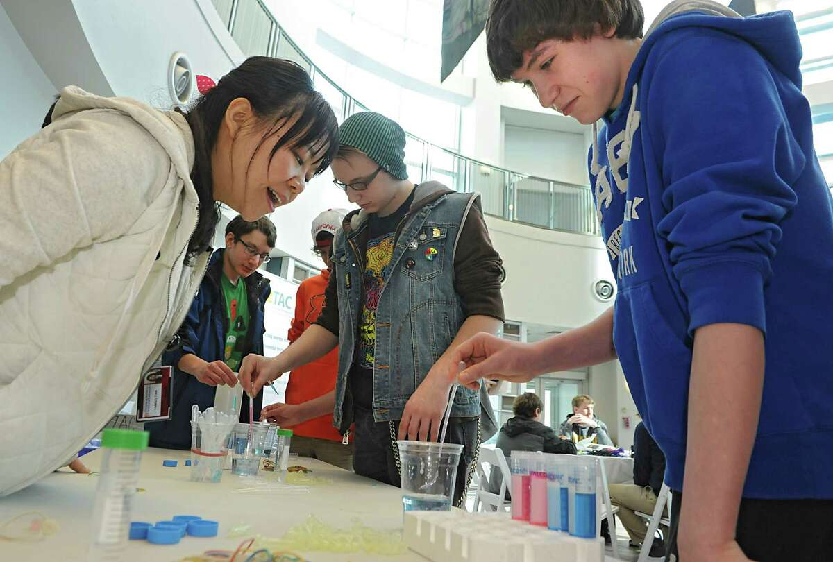 Yangzi Tian, Ph.D. student at Colleges of Nanoscale Science and Engineering, left, watches Jonathan LaPointe, 14, right, and Noah Bosshart, 15, center, as she teaches students from Queensbury High School how to make polymer worms on Thursday, Feb. 5, 2015 in Albany, N.Y. During a NanoCareer Day at SUNY Polytechnic Institute's Colleges of Nanoscale Science and Engineering. (Lori Van Buren / Times Union)
