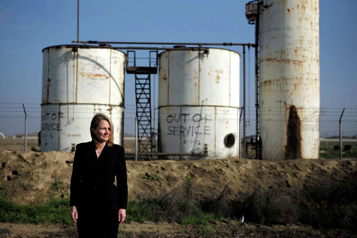 Patricia Oliver, an attorney representing Palla Farms, poses for photos in front of a shutdown injection well located next to Palla Farms' almond orchard, Thursday, Jan. 15, 2015, in Bakersfield, Calif. Palla Farms filed suit blaming several oil companies for contaminating the local groundwater and killing cherry trees. (AP Photo/Jae C. Hong) ORG XMIT: CAJH407