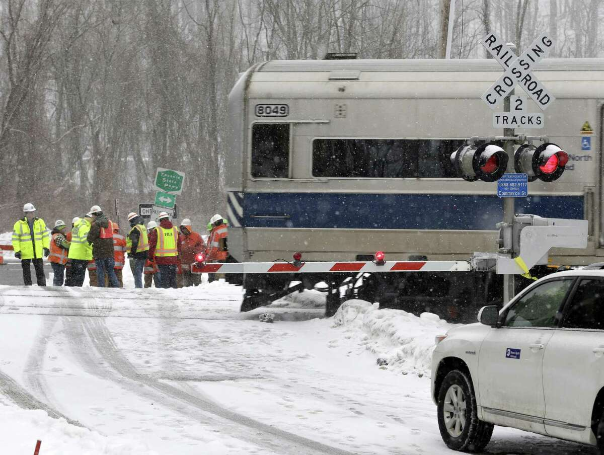A Metro-North Railroad train passes through the intersection that was the site of a fatal collision between an SUV and a commuter train in Valhalla, N.Y., Thursday, Feb. 5, 2015. An investigation into what caused a fiery crash that killed a motorist and five rail riders is focusing on how a mother of three described by friends as safety conscious ended up between two crossing gates in her SUV as a commuter train barreled toward her. (AP Photo/Seth Wenig) ORG XMIT: NYSW104
