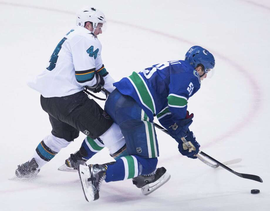 Vancouver Canucks center Bo Horvat (53) fights for control of the puck with San Jose Sharks defenseman Marc-Edouard Vlasic (44) during the second period of an NHL hockey game Thursday, Feb. 5, 2015, in Vancouver, British Columbia. (AP Photo/The Canadian Press, Jonathan Hayward) Photo: JONATHAN HAYWARD / Associated Press / The Canadian Press