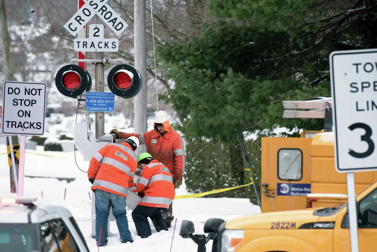 Officials work at the Metro-North Railroad Commerce Street crossing, the site of a deadly crash on Tuesday, in Valhalla, N.Y., Feb. 5, 2015. Engineers and transportation safety experts around the world are working to reduce the dangers of grade-level rail crossings like the one in Valhalla, but human behavior and the laws of physics can defeat even the safest system, researchers say. (Karsten Moran/The New York Times) ORG XMIT: XNYT139