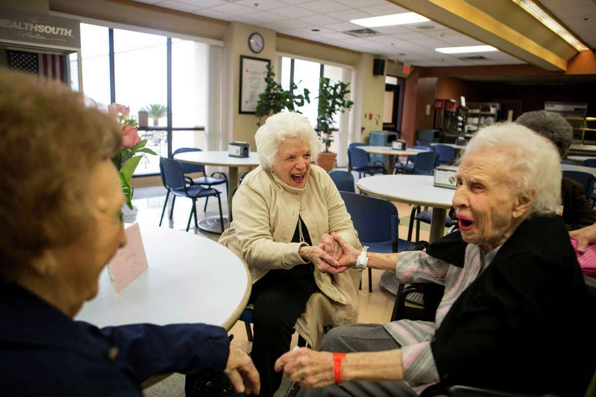 Catherine Olivet, right, reacts to seeing her friends and fellow Wedgwood residents Dorothy Miller, 92, left and Barbara McConnell, 93, for Olivet's 97th birthday at HealthSouth Rehabilitation Institute in San Antonio on Thursday, February 5, 2015.