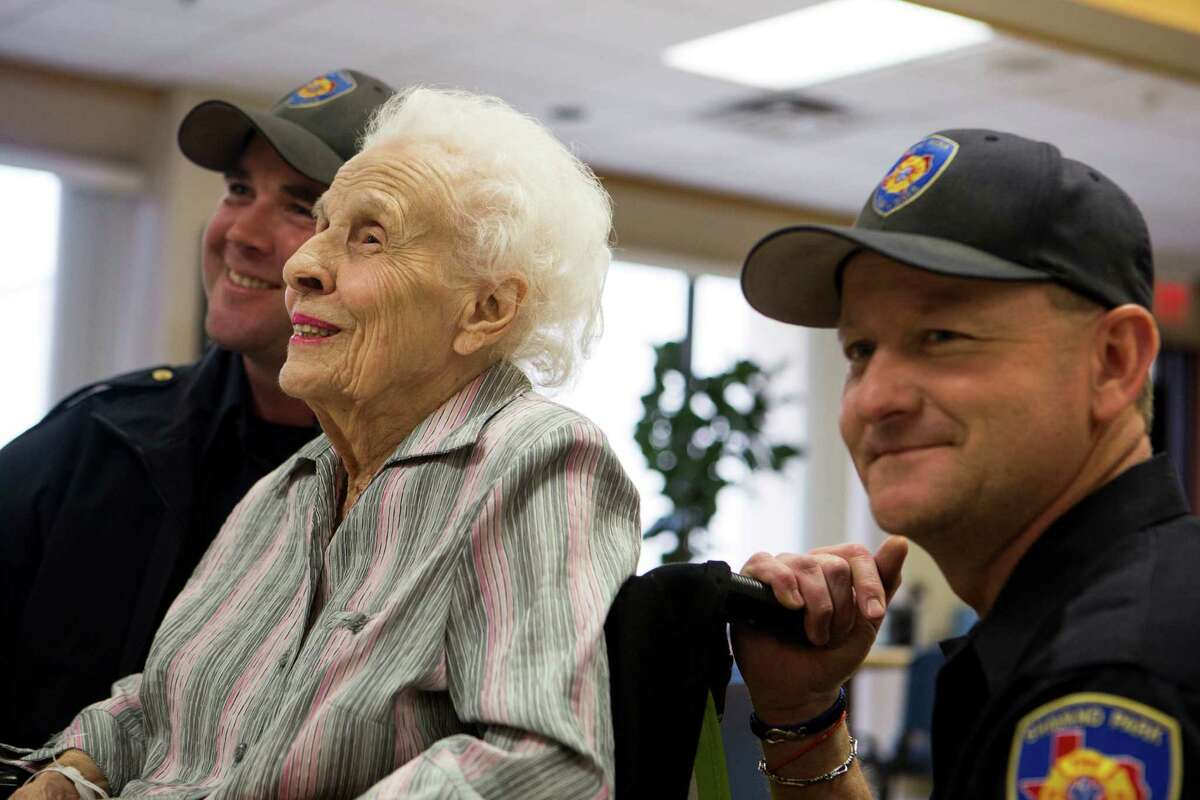 Catherine Olivet, 97, smiled for a photograph with Greg Dehart, left, and Larry Fennell at HealthSouth Rehabilitation Institute in San Antonio on Thursday, February 5, 2015. Dehart and Fennell were two of the Shavano Park firefighters to rescue Olivet and the other residents during the Wedgwood fire.