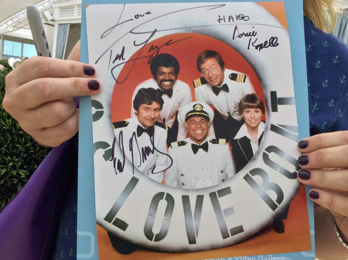 """A fan of the '70s and '80s TV sitcom """"The Love Boat"""" proudly shows off the cast autographs she collected on the Regal Princess cruise with a Love Boat theme."""