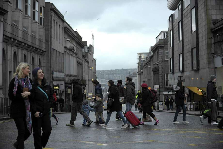 Shoppers walk the streets in central Aberdeen, Scotland in January. On the docks in Aberdeen, oil workers put a brave face on hundreds of job cuts linked to sinking crude prices while union leaders warn that the worst is yet to come. The oil and gas industry has made Aberdeen prosperous; more than half of all jobs in Aberdeen are linked to oil. Photo: ANDY BUCHANAN, AFP / Getty Images / Andy Buchanan