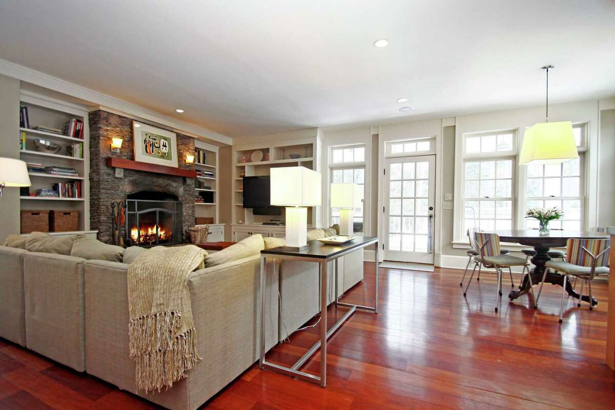 A stone fireplace and wood floor highlight the family room with access to an expansive porch.