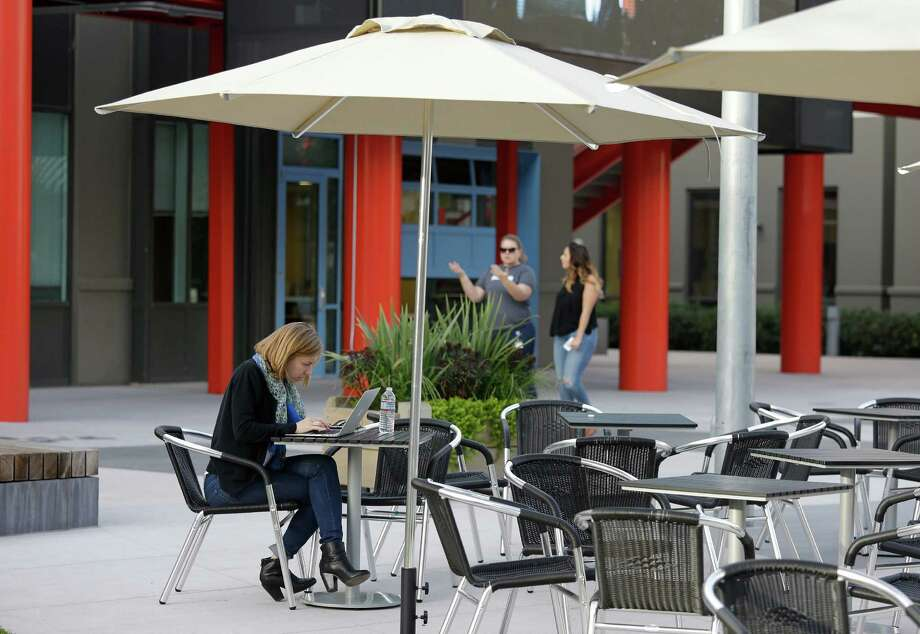 A woman works on her laptop while two others walk by at Facebook's headquarters in Menlo Park. Photo: Eric Risberg / Associated Press / AP