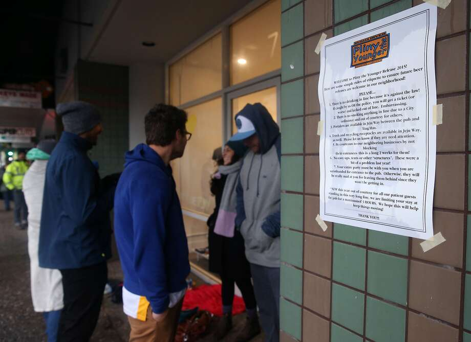 Customers huddle in the doorway of neighboring businesses while they wait for the limited release of Pliny the Younger India Pale Ale at the Russian River Brewing Company in Santa Rosa, Calif. on Friday, Feb. 6, 2015. Beer lovers from across the country wait in long lines for a shot of sipping the IPA, listed at 10.25% ABV, during its 2-week limited availability. Photo: Paul Chinn, The Chronicle