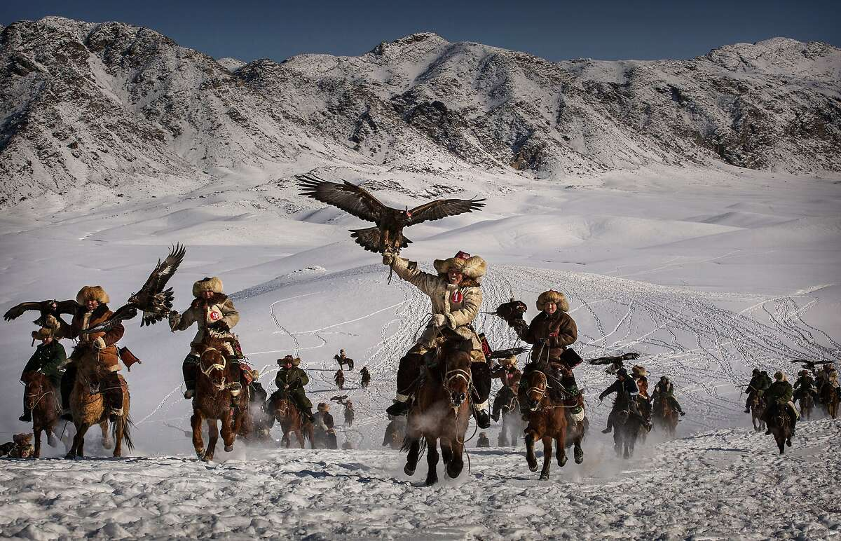 IT'S HORSEBACK HUNTING WITH EAGLES SEASON IN CHINA: Chinese Kazakh eagle hunters ride with their eagles during a local competition in the snow-covered mountains of Qinghe County, Xinjiang, China. The training and handling of the large birds of prey follows a strict set of ancient rules that the eagle hunters are trying to preserve for future generations.