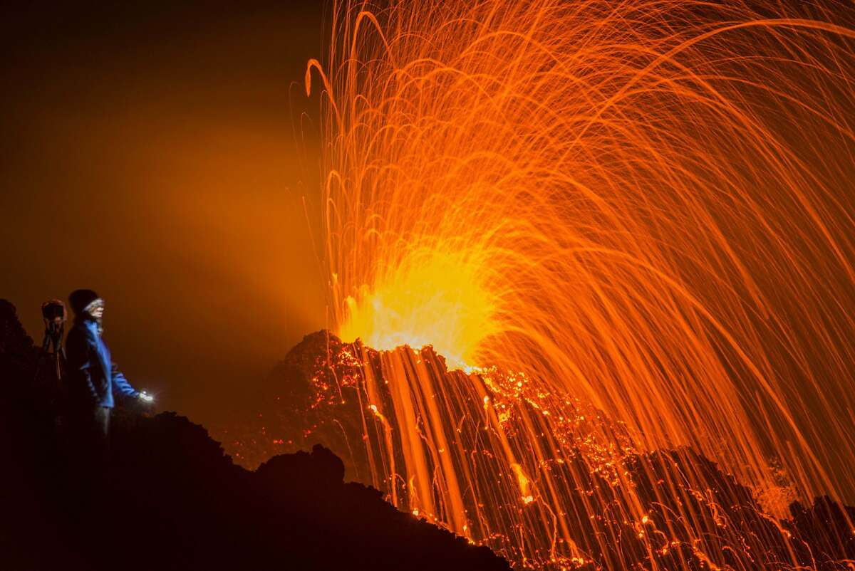 ISLAND ERUPTION: It looks like the Piton de la Fournaise volcano on the French Indian Ocean island of La Reunion is about to spew molten rock on two careless spectators, but they're actually a safe distance away.