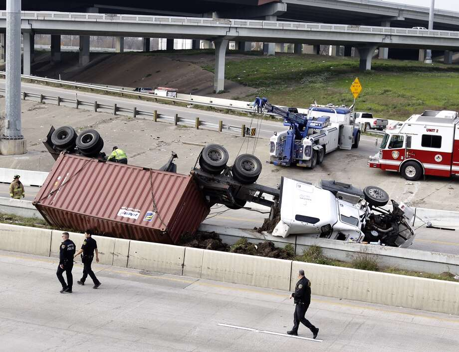 Emergency personal are shown at the scene of an overturned truck along the 59 South ramp to I-10 East Friday, Feb. 6, 2015. / Photo: Melissa Phillip | Houston Chronicle