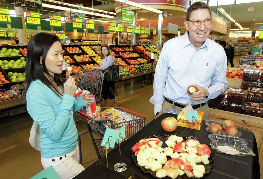 Florence Lim, left, samples an apple as Scott McClelland, H-E-B Houston president, conducts an apple taste test at an H-E-B on Buffalo Speedway. Photo: Melissa Phillip, Staff / © 2014  Houston Chronicle