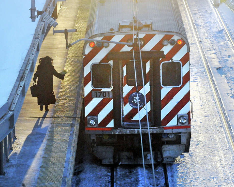 A passenger runs to catch her Metro-North train at the Stamford Train Station, Conn., Thursday, Feb. 5, 2015. Five Metro-North passengers were killed on Tuesday night in Valhalla, N.Y., when the train they were riding in struck an SUV on the tracks inside the railway crossing gates. The driver of that vehicle was also killed in the accident. Photo: Bob Luckey / Greenwich Time