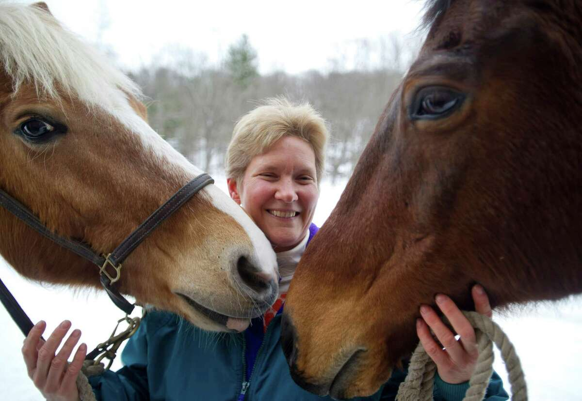Mary-Elizabeth Simpson stands between Willie, left, and Dejay, right, as they cuddle at her North Stamford home on Thursday, January 29, 2015.