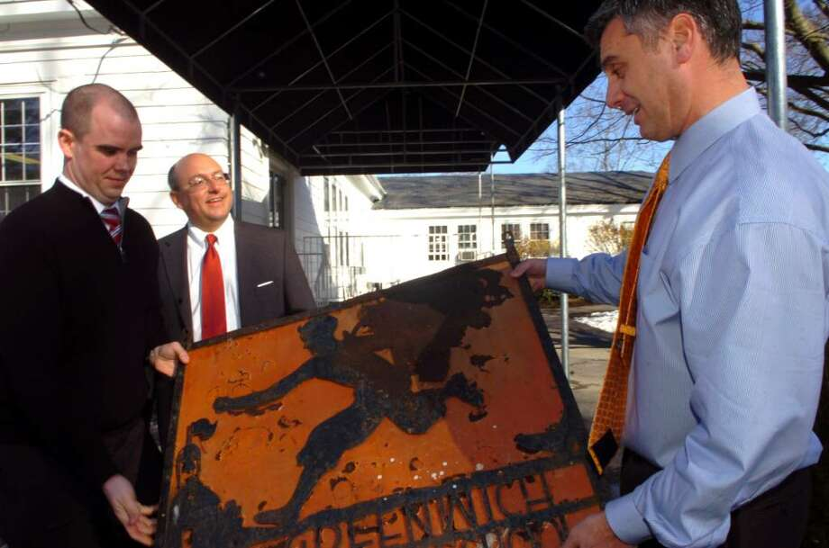 Adam Rohdie, at right,  headmaster of Greenwich Country Day School, admires a sign that was taken from the school in 1967. An anonymous client of Attorney  Phil Russell's took the sign in 1967 and Russell, center is returning it all these years later, on Monday, March, 1, 2010. At left is John Stewart, an associate of Russell, who graduated from Greenwich Country Day School. Photo: Helen Neafsey / Greenwich Time