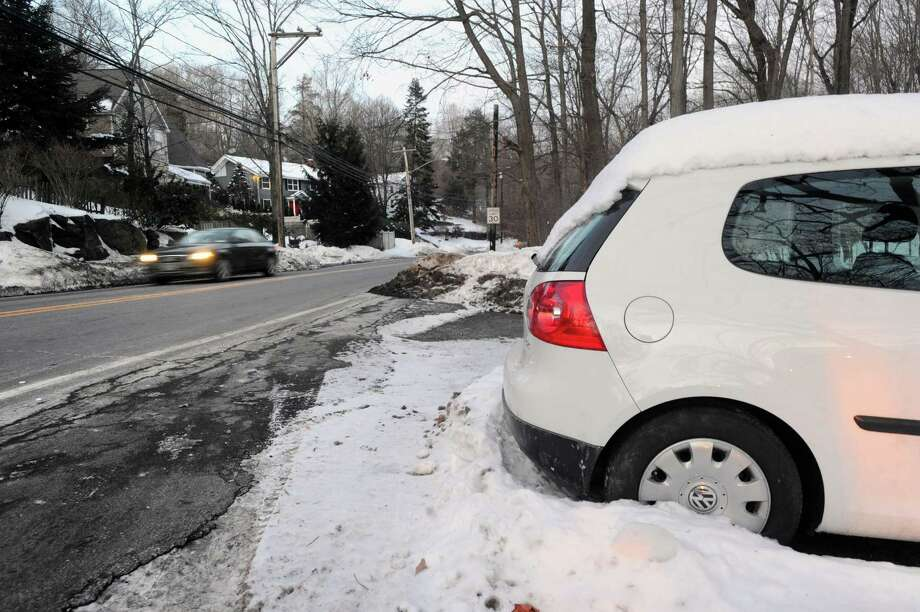 A car covered with snow parked just off Glenville Road, background left, in Greenwich, Conn., Friday, Feb. 6, 2015. Glenville Road now has a new parking restrictions when a snow emergency has been declared by town officials. Photo: Bob Luckey / Greenwich Time