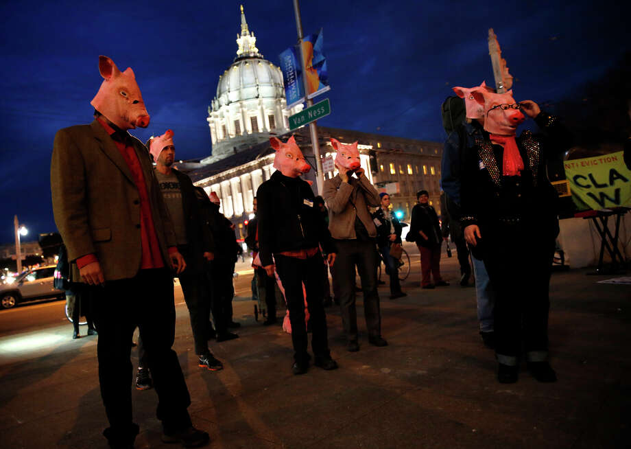 "Protesters wearing pig masks take apart in the ""Crappies"" awards outside the 8th Annual Crunchies awards ceremony at Davies Symphony Hall in San Francisco, Calif. on Thursday, February 5, 2015. Photo: Scott Strazzante / The Chronicle / ONLINE_YES"