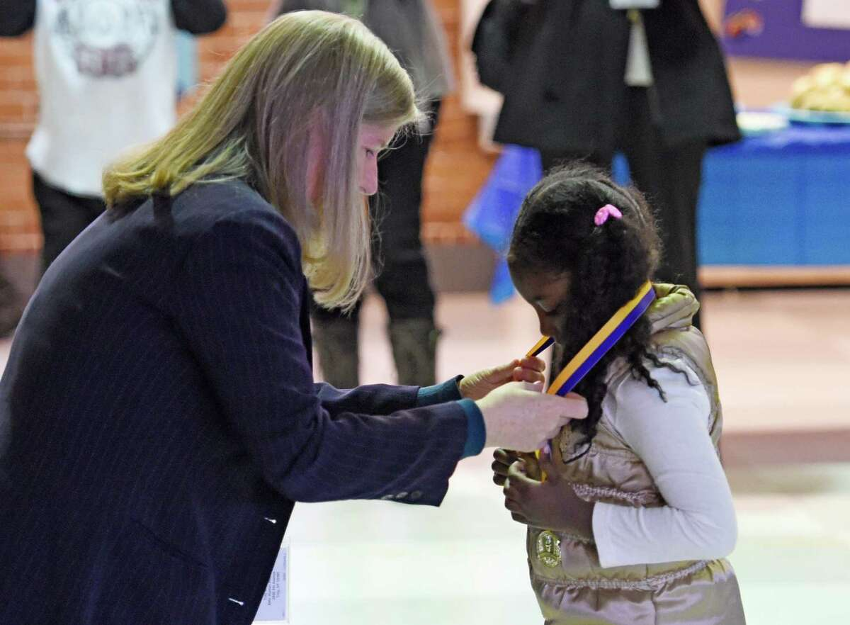 """School principal Cynthia Kilgallon, left presents kindergarten student Ruth Gashaw the Principal's Character Award during a ceremony at School 18 Friday morning Feb. 6, 2015 in Troy, N.Y. The """"Principal's Character Award"""" medal is the highest award given to PS 18 elementary students. The award is based on integrity, character, and the willingness to work hard. (Skip Dickstein/Times Union)"""