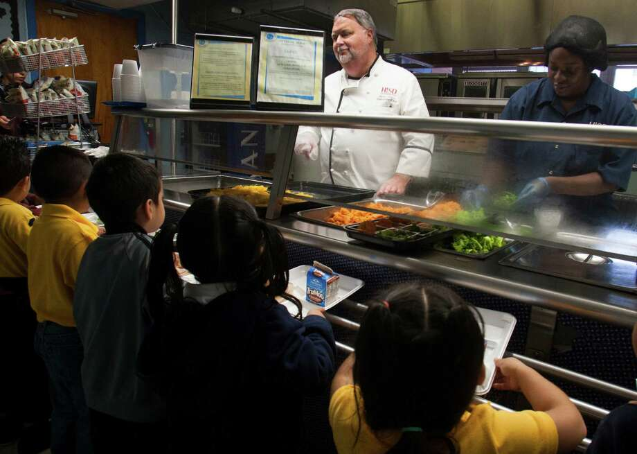 HISD Executive Chef Steve Crisler and Bynetria Briscob serve students lunch at MacGregor Elementary on Friday, Sept. 7, 2012, in Houston. ( J. Patric Schneider / For the Chronicle ) Photo: J. Patric Schneider, Freelance / © 2012 Houston Chronicle