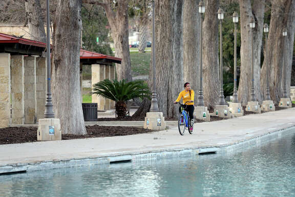 Becky Rodriguez cruises her bike along the still pool of water as people enjoy a winter day at San Pedro Park.
