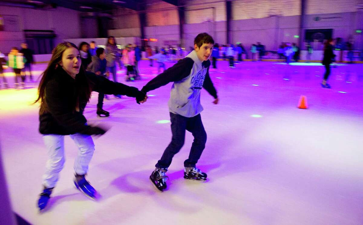 Nicole Chichester, 13, left, and Connor Esposito, 13, right, hold hands as they skate to music under black lights at Twin Rinks in Stamford, Conn., on Friday, February 6, 2015. According to General Manager Robert Rode, the rink sees over 260 teenagers for their free skates on Friday nights from 7:45 to 10 p.m.