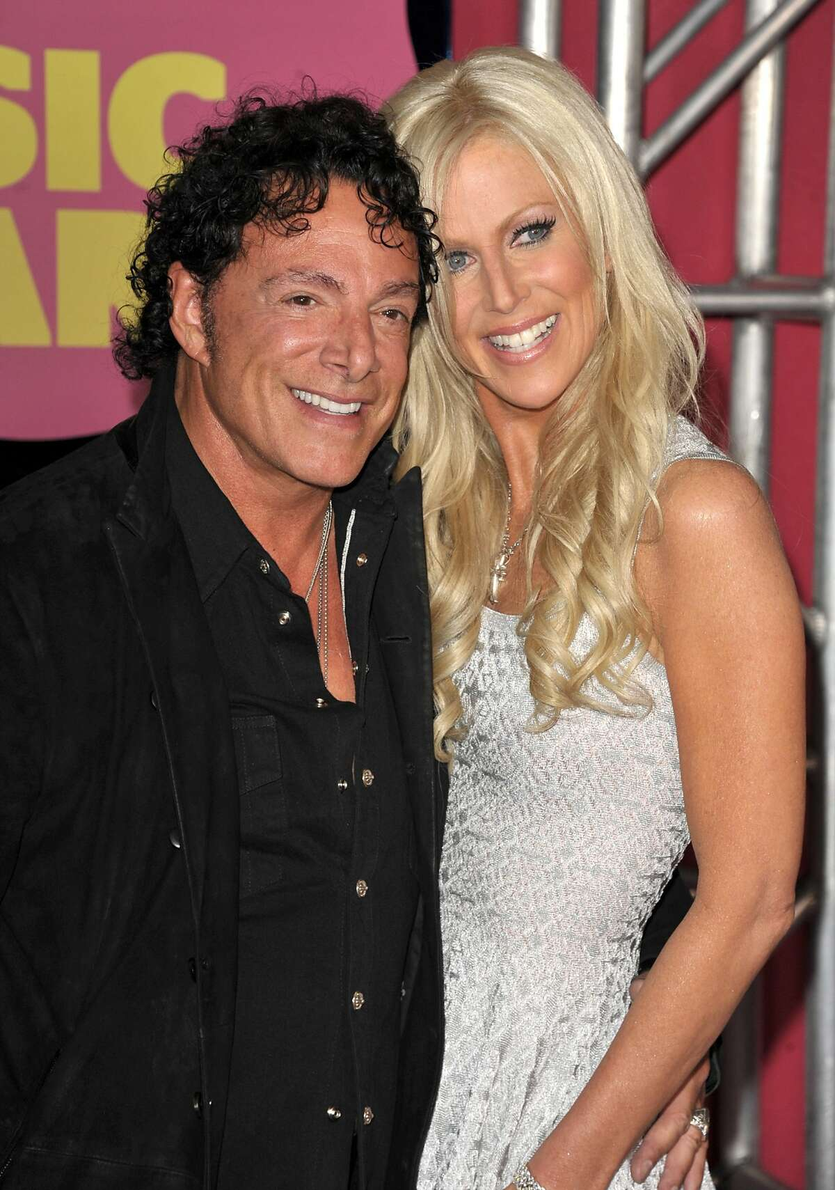 FILE - In this June 6, 2012, file photo, Neal Schon, left, and Michaele Salahi arrive at the CMT Music Awards in Nashville, Tenn. Schon, the lead guitarist and founder of the iconic San Francisco rock band Journey, sued the city Friday, Feb. 6, 2015, over a $240,000 fee to use a city landmark for his lavish wedding to former reality television star Salahi. Schon complains in his federal lawsuit that San Francisco officials unfairly jacked up the fee for the city's permit six days before the wedding after learning the couple planned to broadcast the event as a pay-per-view television show. (Photo by John Shearer/Invision/AP File)