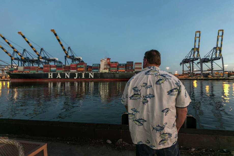 A member of the International Longshore and Warehouse Union looks out last month at the unusually quiet dock at the Port of Los Angeles. A full shutdown of West Coast seaports could come as soon as Monday.  Photo: Damian Dovarganes, STF / AP