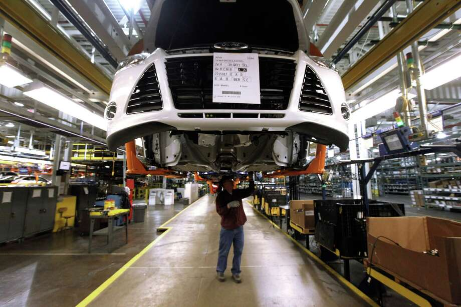 A line worker assembles a Ford Focus at the company's plant in Wayne, Mich. The company might seek to negotiate a contract for lower-paid workers to guarantee work there. Photo: Paul Sancya / Associated Press / AP