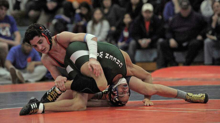New Milford's Mel Ortiz, bottom, and Danbury's Chris Sam wrestle in the 113 pound weight class during the high school wrestling match between New Milford and Danbury high schools on Friday night, February 6, 2015, at Danbury High School, Danbury, Conn. Photo: H John Voorhees III / The News-Times