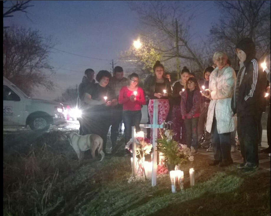 Mourners attend a Friday evening vigil on the Houston street where 18-year-old Vanessa Garcia was killed early in the morning. She was hit by a truck while walking to a school bus stop. Photo: St. John Smith / Houston Chronicle