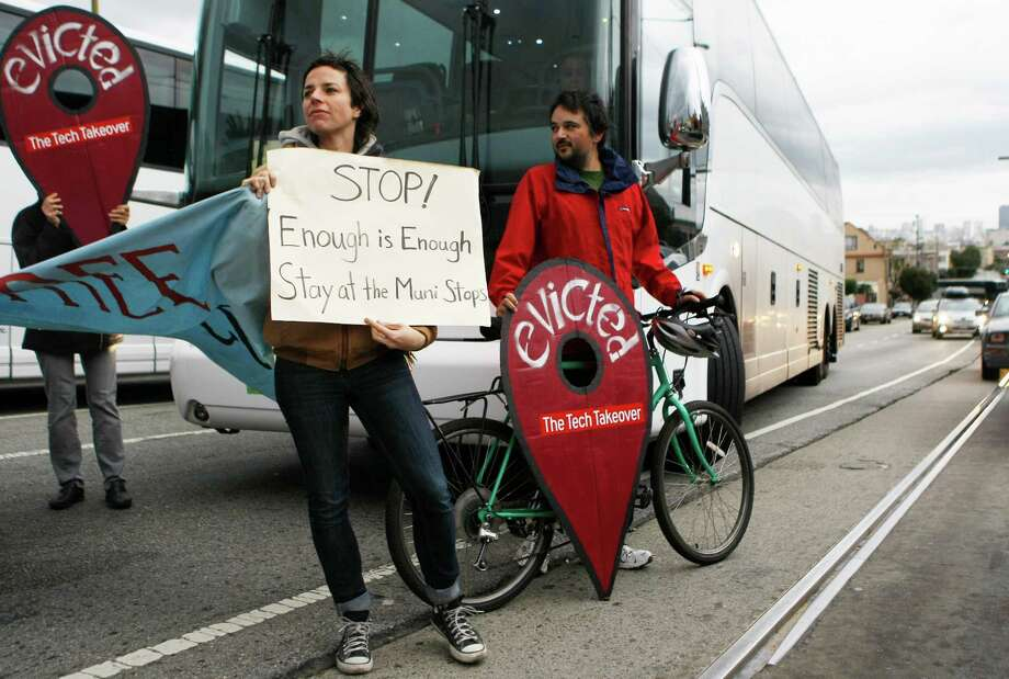 Jordan Reznick (left) and Bevan Richardson block a tech bus at a protest over the buses using parking for parents and teachers of Fairmount Elementary School. Photo: Jessica Christian / The Chronicle / ONLINE_YES