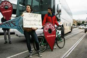 Jordan Reznick (left) and Bevan Richardson block a tech bus at a protest over the buses using parking for parents and teachers of Fairmount Elementary School.