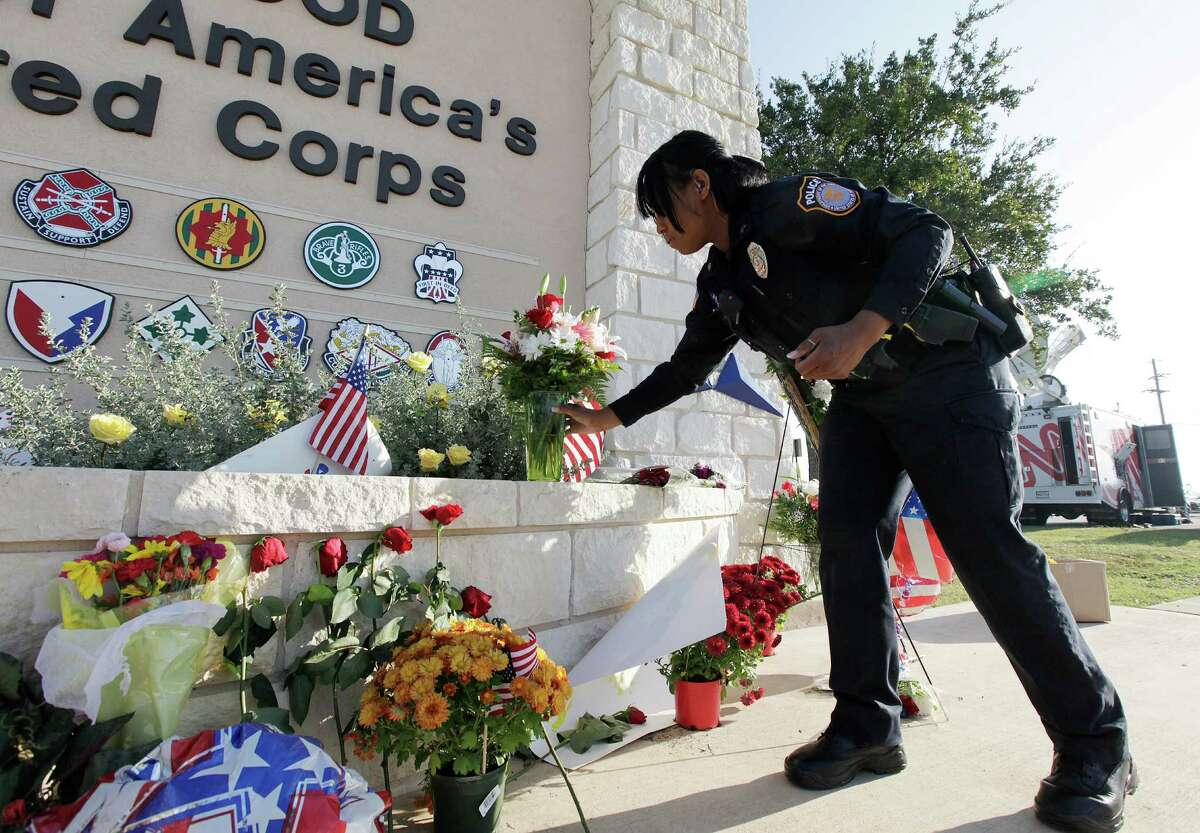 Sgt. Erica Shubrick with the Fort Hood Police Department delivers flowers to the Marvin Leath Visitors Center at the Bernie Beck Main Gate at Fort Hood after the 2009 shooting rampage left 13 dead and more than 30 others wounded.