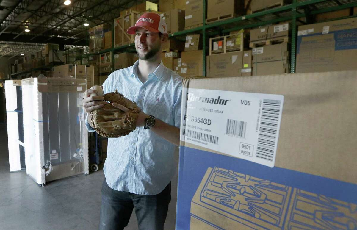 In this Thursday, Jan. 29, 2015, photo, New York Yankees pitcher Chris Martin checks out an old catcher's mitt and ball while visiting the Texas Appliance store warehouse where he used to work in Arlington, Texas. After suffering an injury while on the path to pitching Major League Baseball, Martin had shoulder surgery in 2007 and his throwing arm didn?'t respond so he figured his baseball career was over. After a while he started to work at Texas Appliance with a friend and in 2010, the pair started throwing a baseball in the warehouse during down time. Soon Martin realized his shoulder felt good and he began his return to pitching. (AP Photo/LM Otero) ORG XMIT: DN204