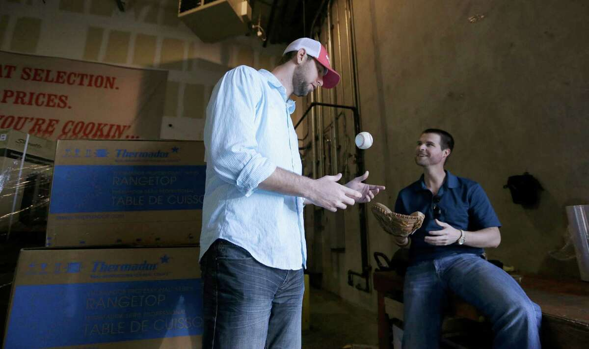 In this Thursday, Jan. 29, 2015, photo, New York Yankees pitcher Chris Martin, left, playfully tosses a baseball as his high school buddy Jordan Bostick watches at the Texas Appliance store warehouse where they used to work together and play catch in Arlington, Texas. After suffering an injury while on the path to pitching Major League Baseball, Martin had shoulder surgery in 2007 and his throwing arm didn?'t respond so he figured his baseball career was over. After a while he started to work at Texas Appliance with his friend Bostick and in 2010, the pair started throwing a baseball in the appliance store warehouse during down time. Soon Martin realized his shoulder felt good and he began his return to pitching. (AP Photo/LM Otero) ORG XMIT: DN203