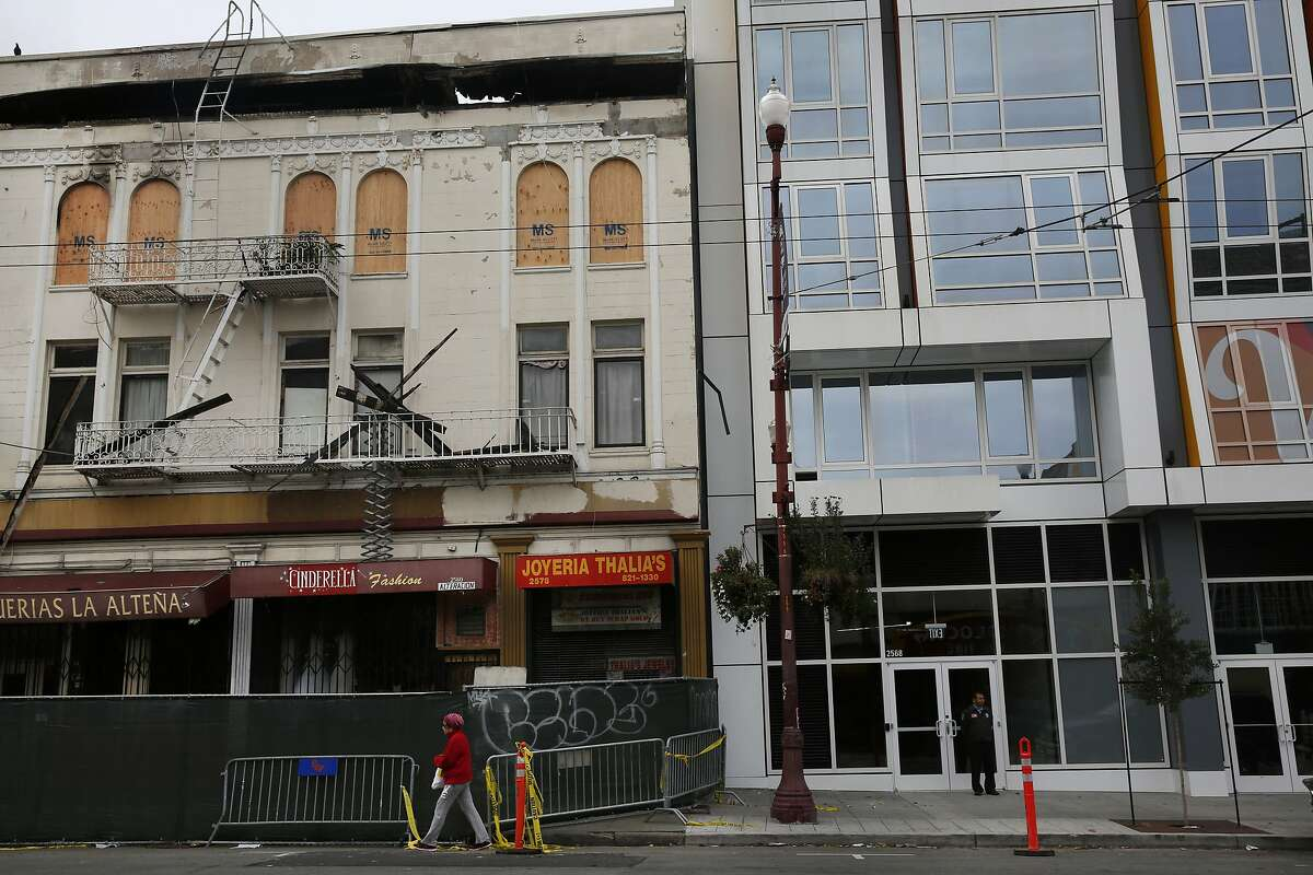A pedestrian walks past the burned out Mission Market next to the new Vida condos in the Mission Feb. 6, 2015 in San Francisco, Calif.