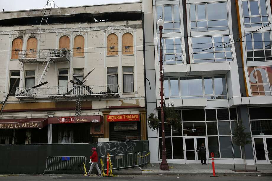 A pedestrian walks past the burned out Mission Market next to the new Vida condos in the Mission Feb. 6, 2015 in San Francisco, Calif. Photo: Leah Millis, The Chronicle