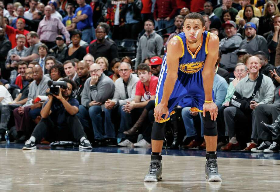 Stephen Curry, standing during free throws in the final seconds, and the Warriors played well in Friday night's showdown of the NBA's top teams in Atlanta, but the Hawks were a bit better on every count. Photo: Kevin C. Cox / Getty Images / 2015 Getty Images