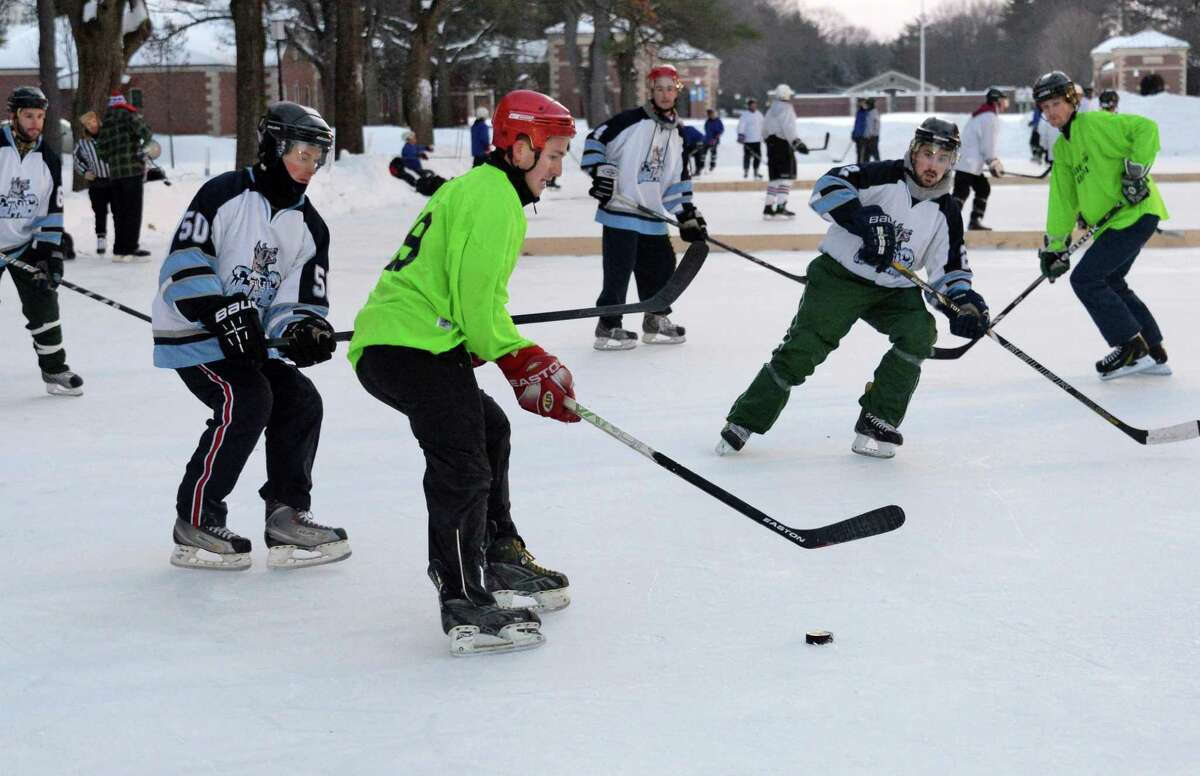 Riley Hill of Malta, center, plays on the Blades of Glory team from Malta against the Connecticut team, Stagnetti's Revenge during the 2nd Annual Saratoga Frozen Springs Classic at Saratoga Spa State Park Friday Feb. 6, 2015, in Saratoga Springs, NY. (John Carl D'Annibale / Times Union)