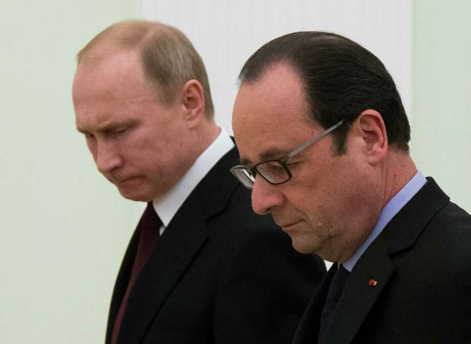 Russian President Vladimir Putin, left, and French President Francois Hollande, enter a hall for their and German Chancellor Angela Merkel talks in the Kremlin in Moscow, Russia, Friday, Feb. 6, 2015. Talks among the leaders of Russia, France and Germany on a peace initiative for Ukraine ended early Saturday with an announcement that Russian President Vladimir Putin and his Ukrainian counterpart would discuss a proposal to end the fighting in a four-way telephone call this weekend.(AP Photo/Alexander Zemlianichenko) Photo: Alexander Zemlianichenko / Associated Press / AP