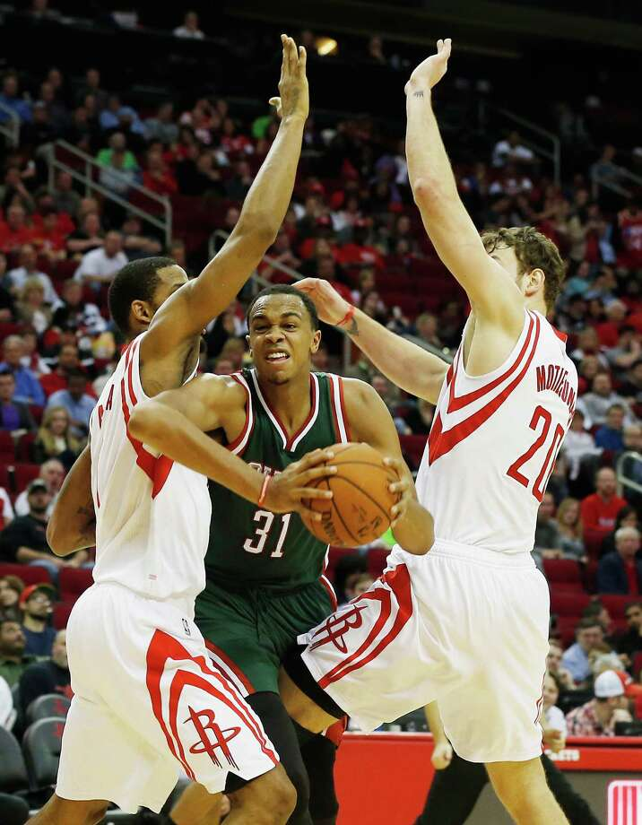 The Bucks' John Henson, center, tries to squeeze through a defensive opening between the Rockets' Trevor Ariza and Donatas Motiejunas on Friday night at Toyota Center. Photo: Scott Halleran, Staff / 2015 Getty Images