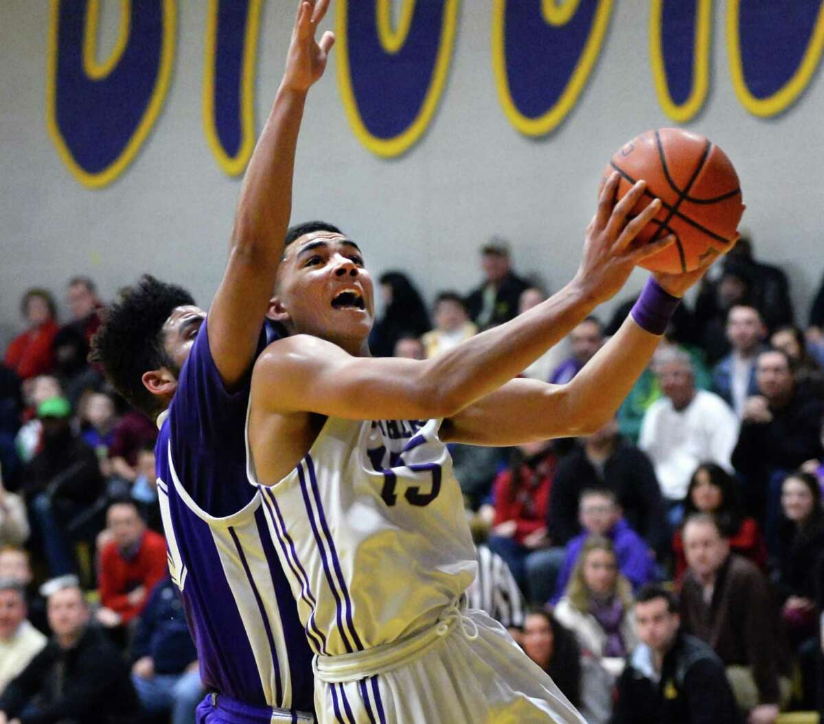 CBA's #15 Mike Wynn, right, is fouled by CCHS's #00 Gabe Woodley as he goes to the basket in Friday's game at CBA Feb. 6, 2015, in Colonie, NY. (John Carl D'Annibale / Times Union)