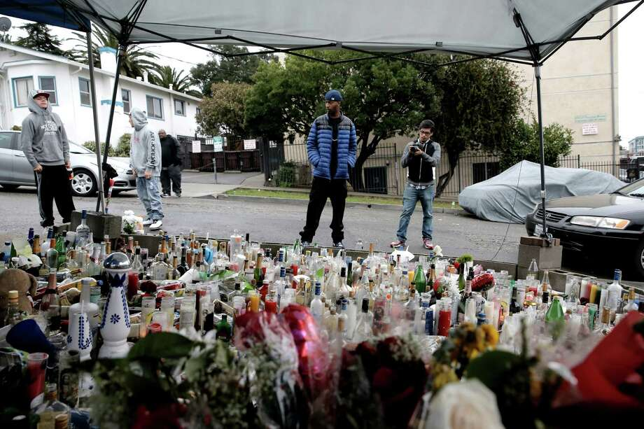 Rap artist O-ZONE, (center) on Friday Feb. 6, 2015, looks over a memorial dedicated to his mentor, The Jacka who was slain last week near MacArthur Blvd. and 94th Ave. in Oakland, Ca. Director/editor Luis Montoya, (right) video tapes the event for use in a rap video. Photo: Michael Macor / The Chronicle / ONLINE_YES