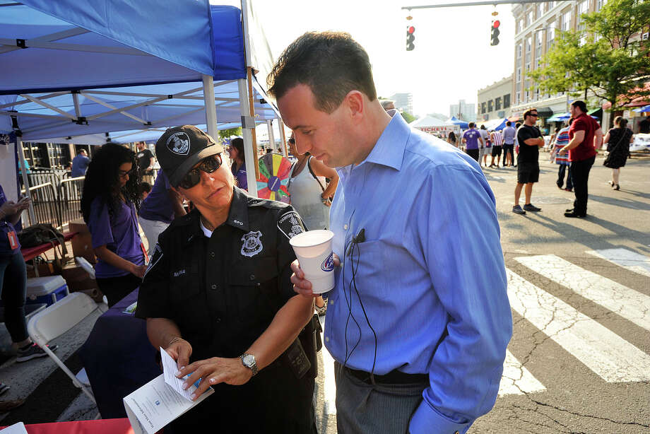 Officer Adriana Molina shows Tony Smyth recruitment materials at the Stamford Police recruitment booth at Alive@Five concert event in Columbus Park in Stamford, Conn., on Thursday, Jul 31, 2014. Photo: Jason Rearick / Stamford Advocate