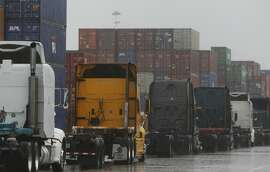 Trucks line up at the Port of Oakland in Oakland, Calif. Friday, February 6, 2015, waiting for containers from incoming cargo ships to be loaded on their beds. Union-led work slowdowns have been occurring on 29 west coast ports, piling up trucks and ships at each location.