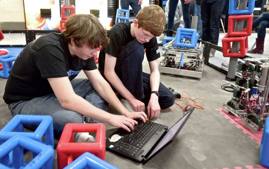 Senior Anthony Folino, 17, left, and junior Benjamin Hellmann, 16, from Danbury High School work on the programing for the team 5150F robot in-between qualifying rounds of the VEX Robotics event held at DHS on Saturday, February 7, 2015, in Danbury, Conn. Folino is the lead programer for all four of Danbury's teams. Photo: H John Voorhees III / The News-Times