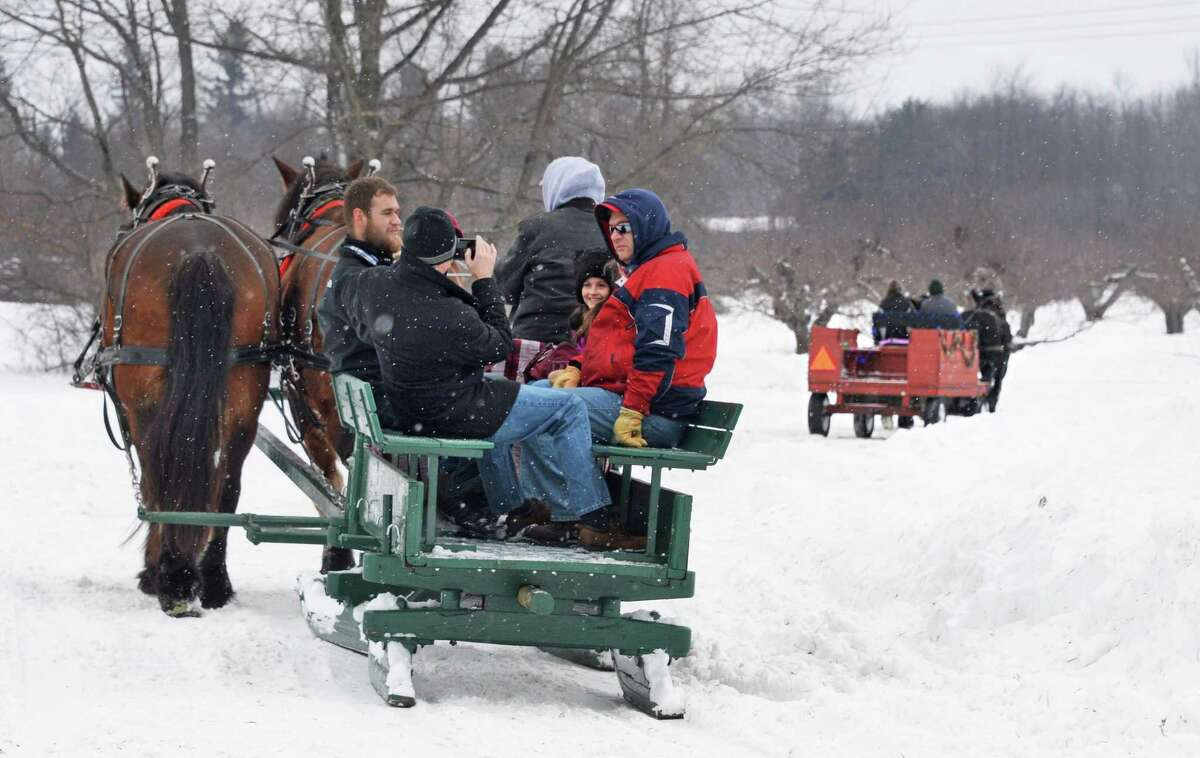 Festival goers are treated to a horse drawn sleigh ride through the orchards at Riverview Orchards as part of the annual Clifton Park WinterFest Saturday Feb. 7, 2015, in Clifton Park, NY. (John Carl D'Annibale / Times Union)