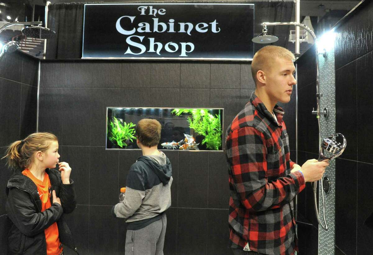Salesman Brendan Wagner of The Cabinet Shop shows off a shower with built-in aquarium during the Times Union Home Expo at the Times Union Center on Saturday Feb. 7, 2015 in Albany , N.Y. (Michael P. Farrell/Times Union)