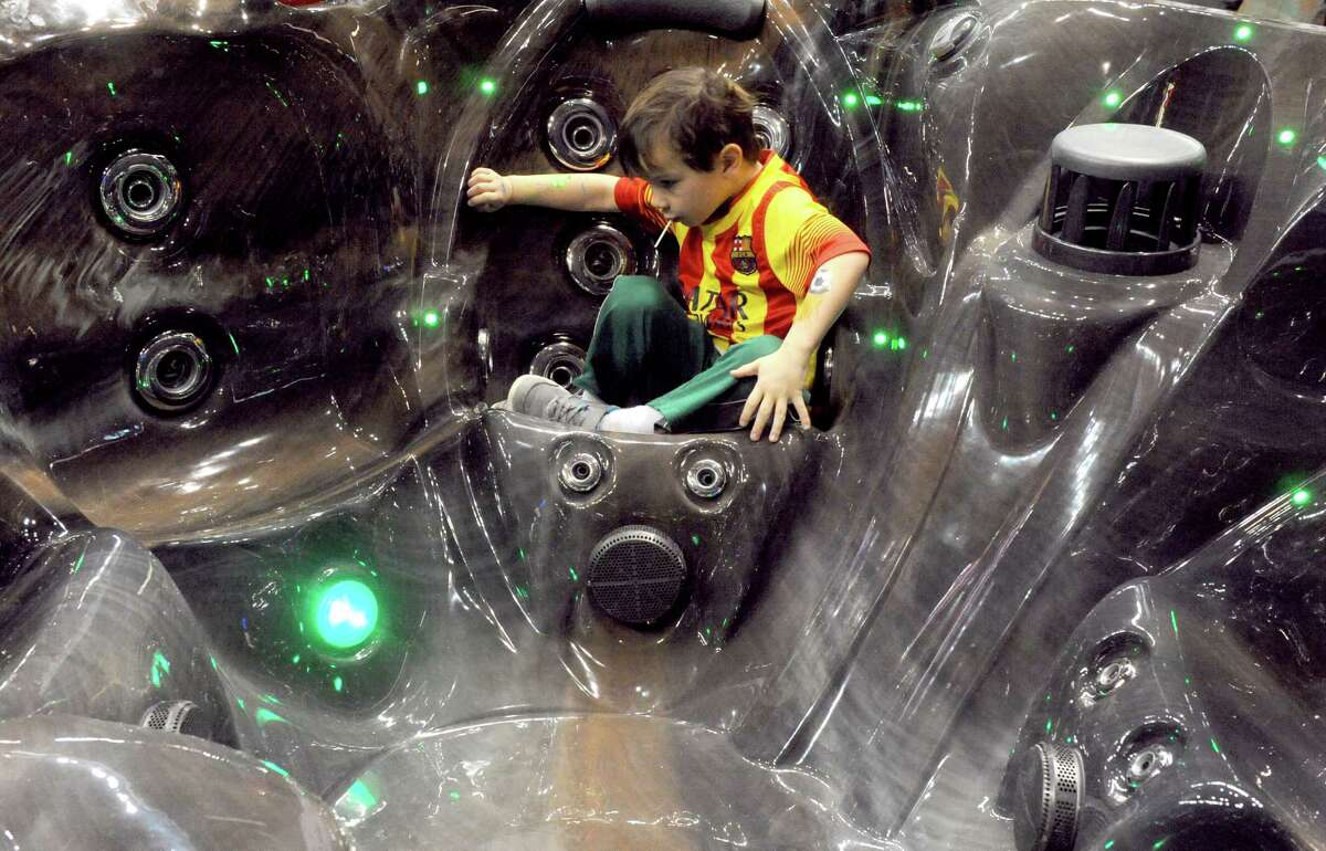 Five-year-old Scott Hutton of Slingerlands sits in an Islander Pools and Spas hot tub his family was looking at during the Times Union Home Expo at the Times Union Center on Saturday Feb. 7, 2015 in Albany , N.Y. (Michael P. Farrell/Times Union)